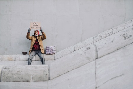Homeless beggar man sitting in city holding cardboard sign. Copy space. Stock Photo
