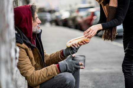 Unrecognizable woman giving food to homeless beggar man sitting in city. Imagens