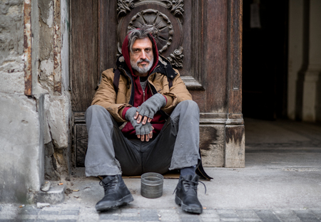 Homeless beggar man sitting outdoors in city asking for money donation. Stockfoto - 112649521