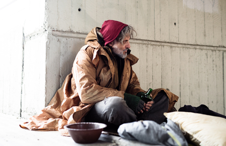 Homeless beggar man sitting outdoors in city asking for money donation. Imagens