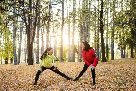Two female runners stretching outdoors in forest in autumn nature.