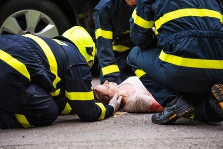 Trzech strażaków pomaga młodej rannej kobiecie leżącej na drodze po wypadku.