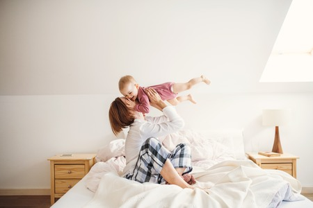 A young mother with little daughter sitting indoors on bed in the morning, playing. Stock Photo