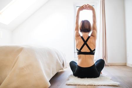 Una vista trasera de una mujer joven que hace ejercicio en el interior de un dormitorio. Copie el espacio. Foto de archivo