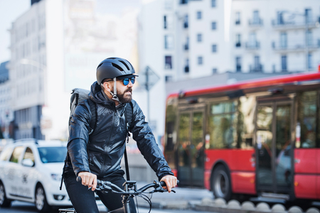 Male courier with bicycle delivering packages in city. Copy space. Reklamní fotografie