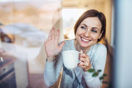 Une jeune femme avec une tasse de café regardant par la fenêtre, saluant.