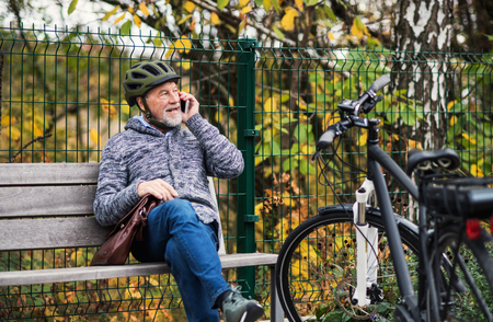 Senior man with electrobike sitting on a bench outdoors in town, using smartphone.