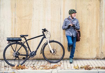 Aktiver älterer Mann mit Elektrofahrrad, der draußen in der Stadt steht, mit Smartphone. Standard-Bild