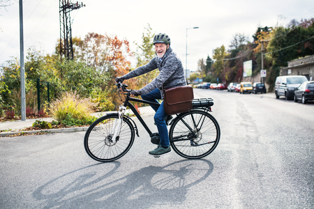 Active senior man with electrobike cycling outdoors in town. Stock Photo