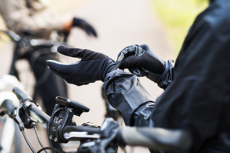 A close-up of a cyclist with electrobike putting on gloves outdoors in park.