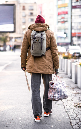 A rear view of homeless beggar man walking outdoors in city, holding bag.