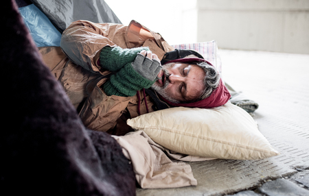 Homeless beggar man lying on the ground outdoors in city, warming up hands.