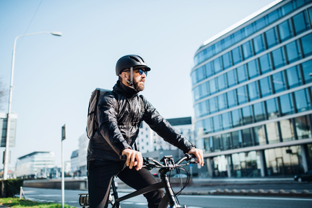 Male courier with bicycle delivering packages in city. Copy space. Stockfoto
