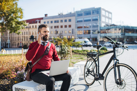 Businessman commuter with electric bicycle sitting on bench, using laptop and smartphone.