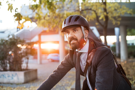 Hipster businessman commuter with bicycle traveling home from work in city.