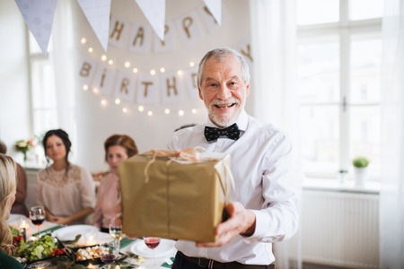 A senior man holding a present in a box on a indoor family birthday party.