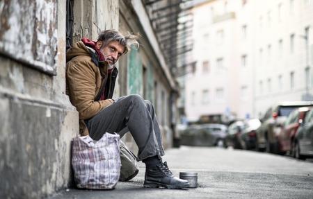 Homeless beggar man sitting outdoors in city, asking for money donation.