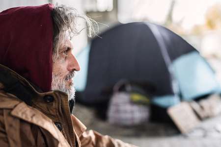 A side view portrait of homeless beggar man sitting outdoors. Copy space. Imagens