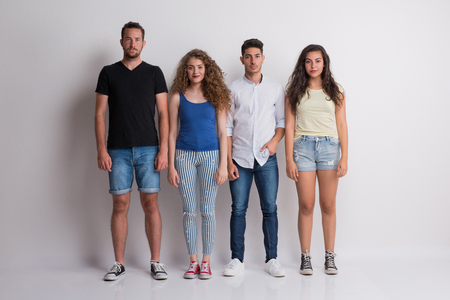 Joyful young group of friends standing in a studio, looking at camera.