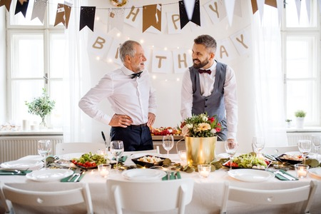 A portrait of a senior and mature man standing indoors in a room set for a party. Stock Photo