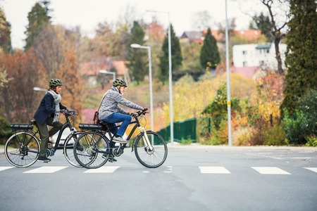 Active senior couple with electrobikes outdoors crossing a road in town.