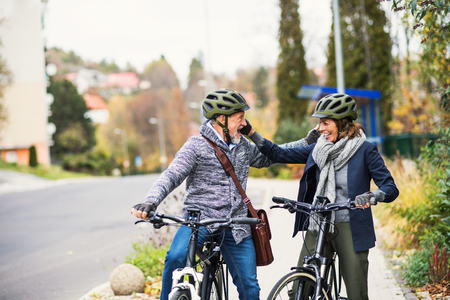 Active senior people with electrobikes greeting outdoors on a road in town. Stock Photo
