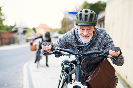 Active senior couple with electrobikes standing outdoors on a road in town.