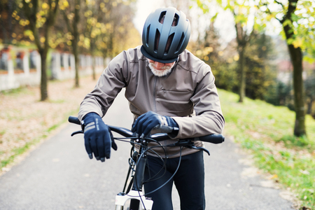 Active senior man with electrobike standing outdoors on a road in nature.
