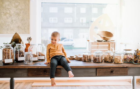 A barefoot small toddler boy sitting on a table in zero waste shop. Stock Photo