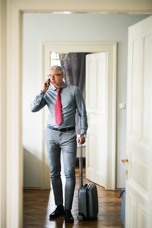Mature businessman on a business trip standing in a hotel room, using smartphone. Banco de Imagens