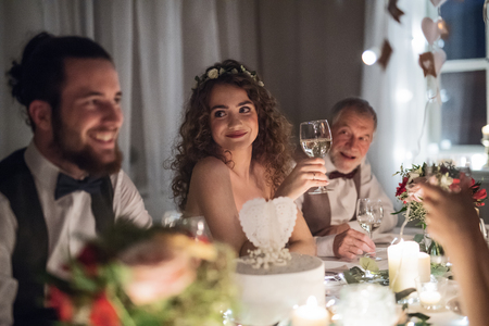 A young couple sitting at a table on a wedding, talking to guests. Stock Photo