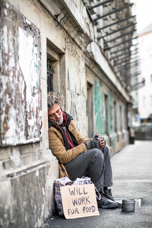 Homeless beggar man sitting outdoors in city asking for money donation. Stock Photo