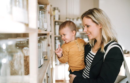 A young woman with a toddler boy buying groceries in zero waste shop. 스톡 콘텐츠