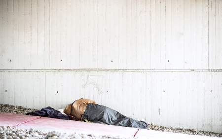 A rear view of homeless beggar man lying on the ground outdoors in city, sleeping.
