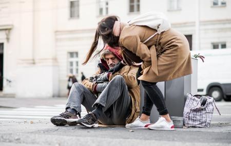 Junge Frau, die dem obdachlosen Bettler Geld gibt, der in der Stadt sitzt.