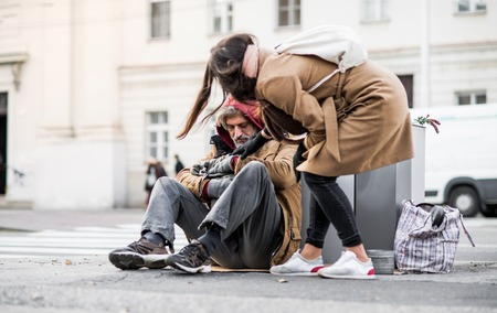 Young woman giving money to homeless beggar man sitting in city. Stock fotó - 115295263