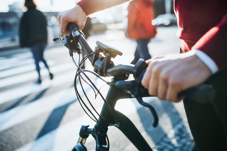 A midsection of businessman commuter with electric bicycle traveling to work in city. Stock Photo