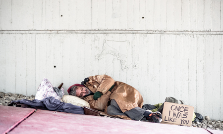 Homeless beggar man lying on the ground outdoors in city, sleeping. Copy space.