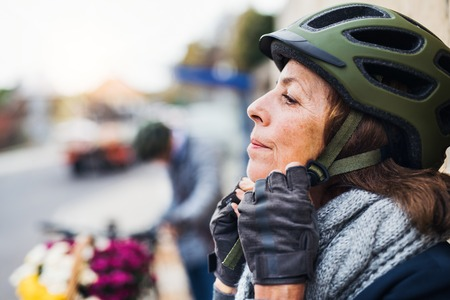 Active senior woman standing outdoors in town, putting on a bike helmet. Copy space. Stock Photo
