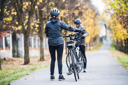 Active senior couple with electrobikes standing outdoors on a road in park. Stock Photo