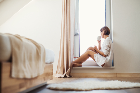 A young woman with night shirt sitting by the window in the morning.