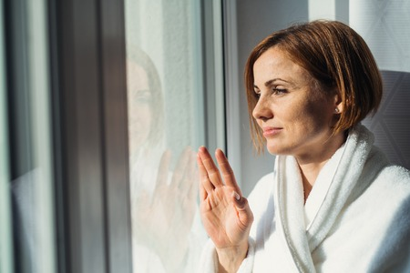 A young woman with bathrobe standing by the window in the morning, looking out.