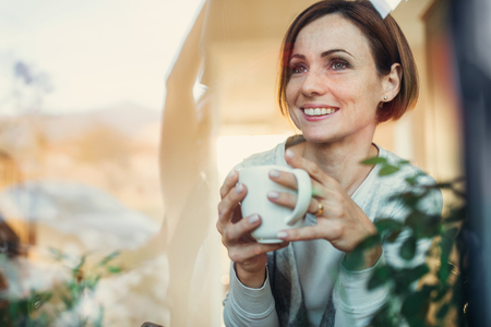A young woman with cup of coffee looking out of a window. Shot through glass. Stock Photo