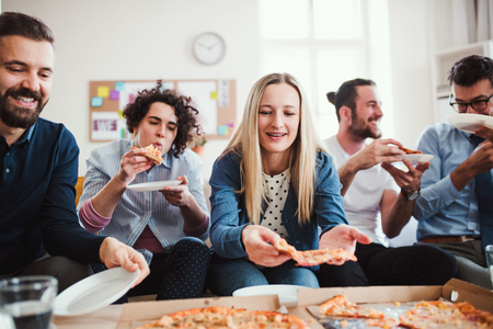 Group of young businesspeople with pizza having lunch in a modern office. Stock Photo