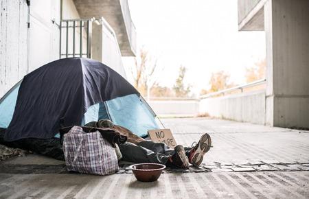 Nogi i stopy bezdomnego żebraka człowieka leżącego na ziemi w mieście, śpiącego w namiocie.
