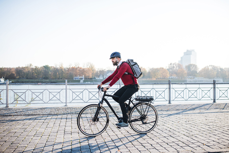 Hipster businessman commuter with electric bicycle traveling to work in city. 写真素材 - 115657523