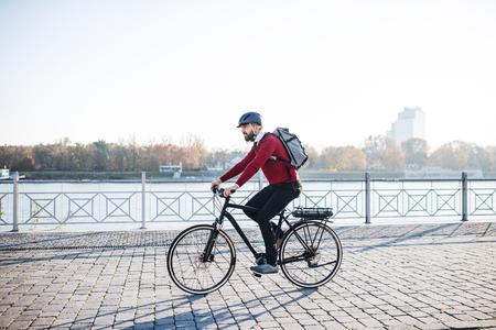 Viajero de empresario hipster con bicicleta eléctrica viajando al trabajo en la ciudad.
