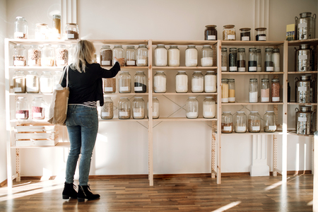 A young happy woman buying groceries in zero waste shop. Copy space. Stockfoto