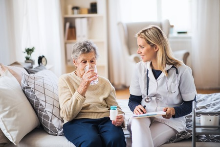 A health visitor and a senior woman at home, taking pills. Stock fotó