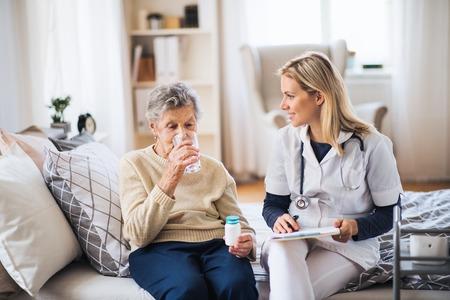 Pielęgniarka środowiskowa i starsza kobieta w domu, zażywająca pigułki. Zdjęcie Seryjne